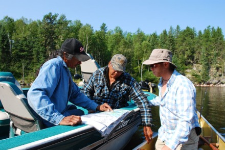 Jordan and two native guides look at map to find good fishing spots